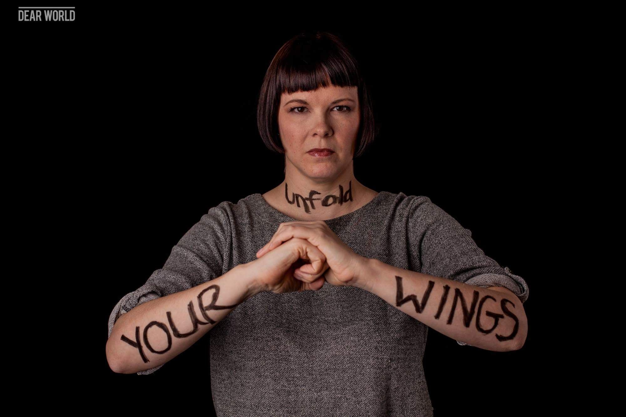 """woman with """"unfold your wings"""" written on her arms"""